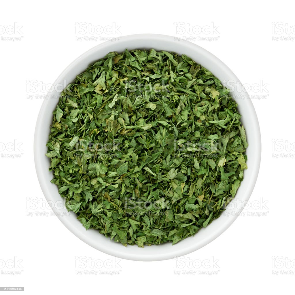 Dried Parsley Flakes in a Ceramic Bowl stock photo