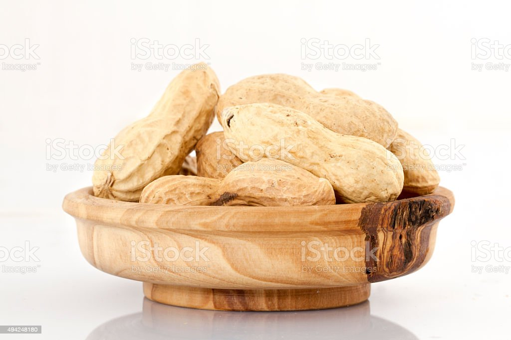 Dried peanuts in isolated on white in a wooden bowl stock photo