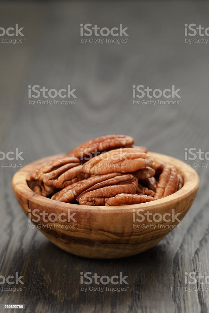 dried pecan nuts in olive bowl on wood table stock photo