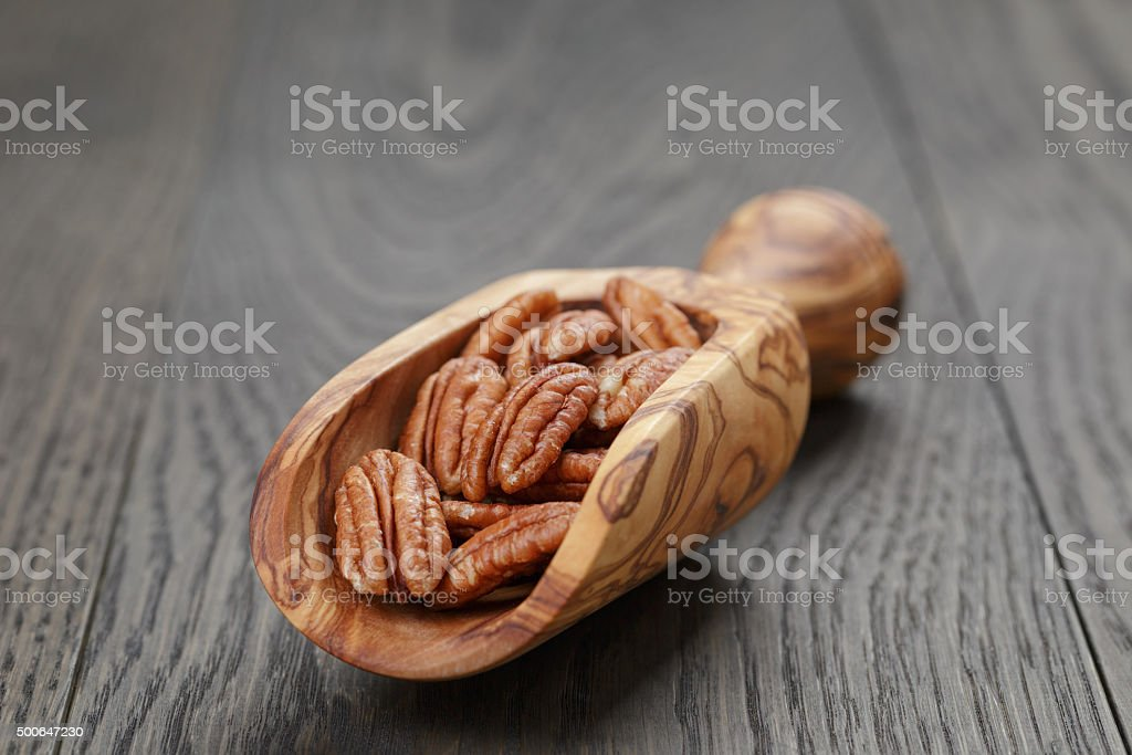 dried pecan nuts in olive scoop on wood table stock photo