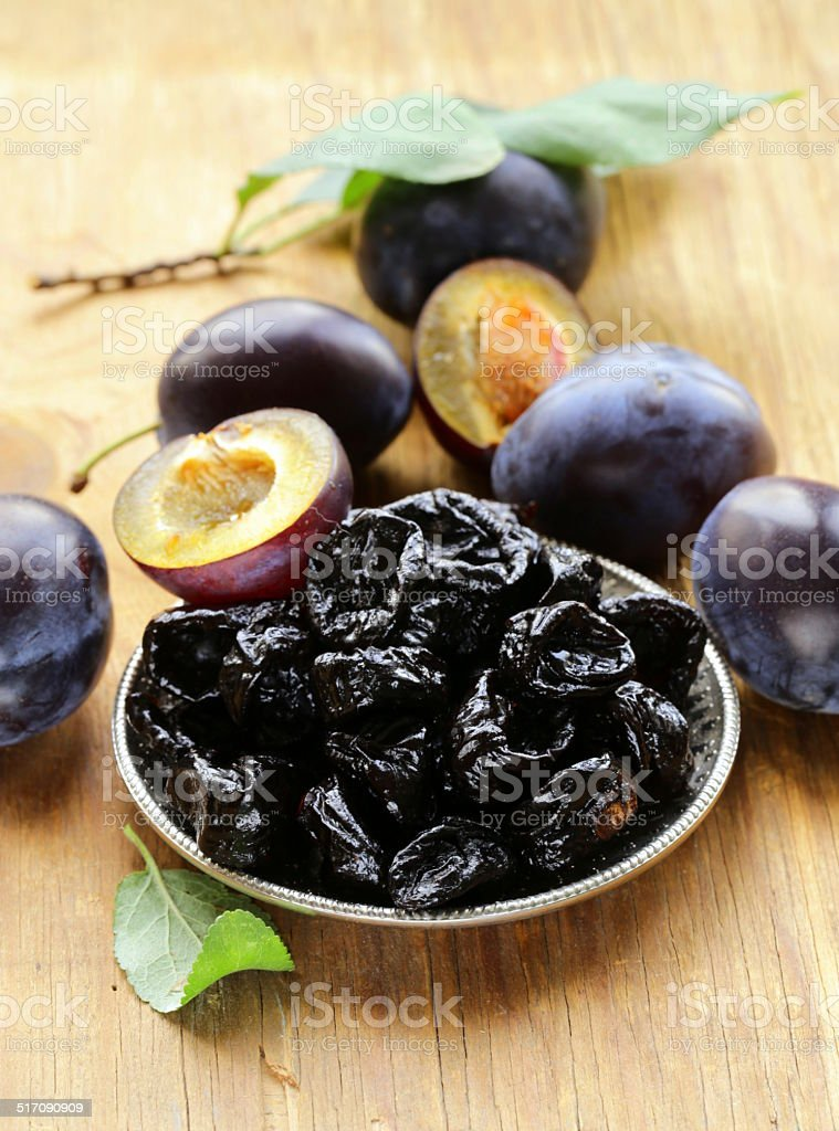 Dried plums prunes and fresh berries on the wooden table stock photo