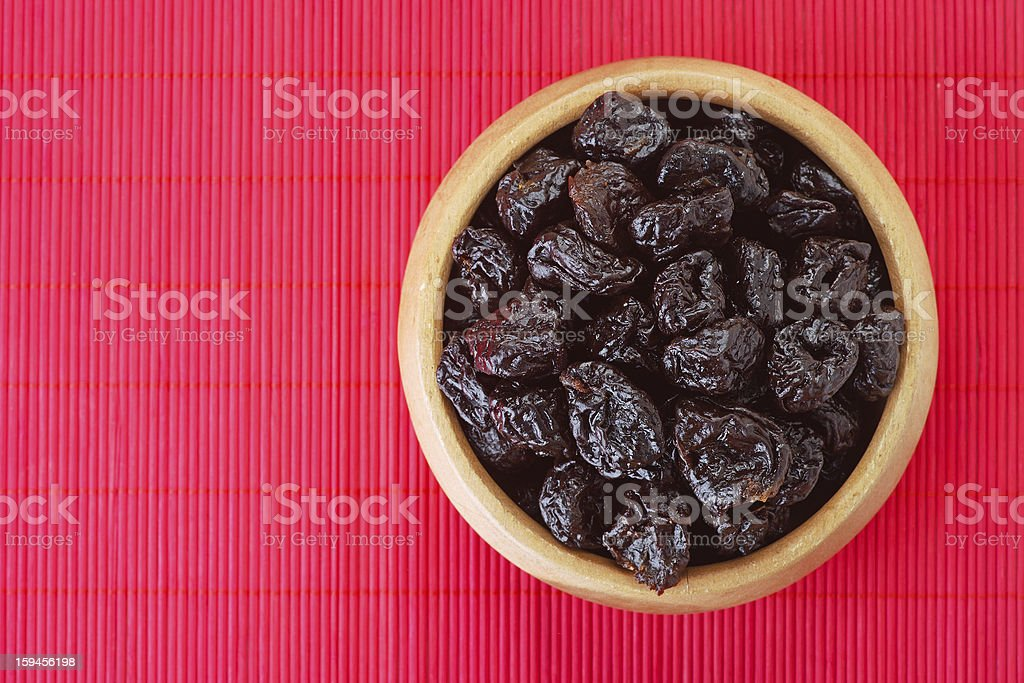 Dried prunes in wooden bowl royalty-free stock photo