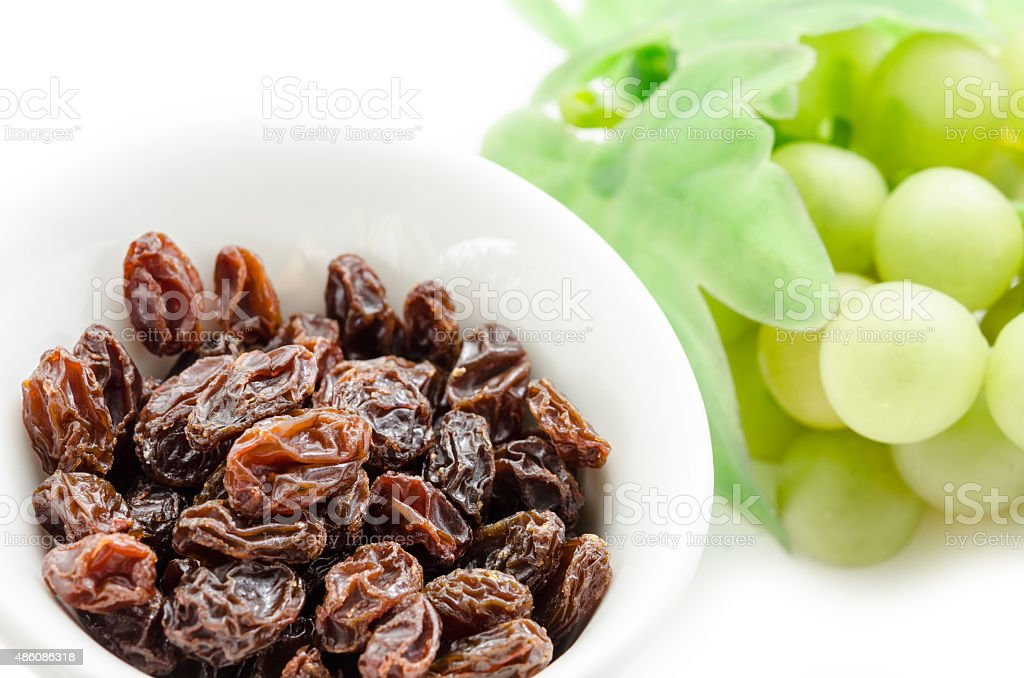 Dried raisins in white cup and fresh grapes stock photo