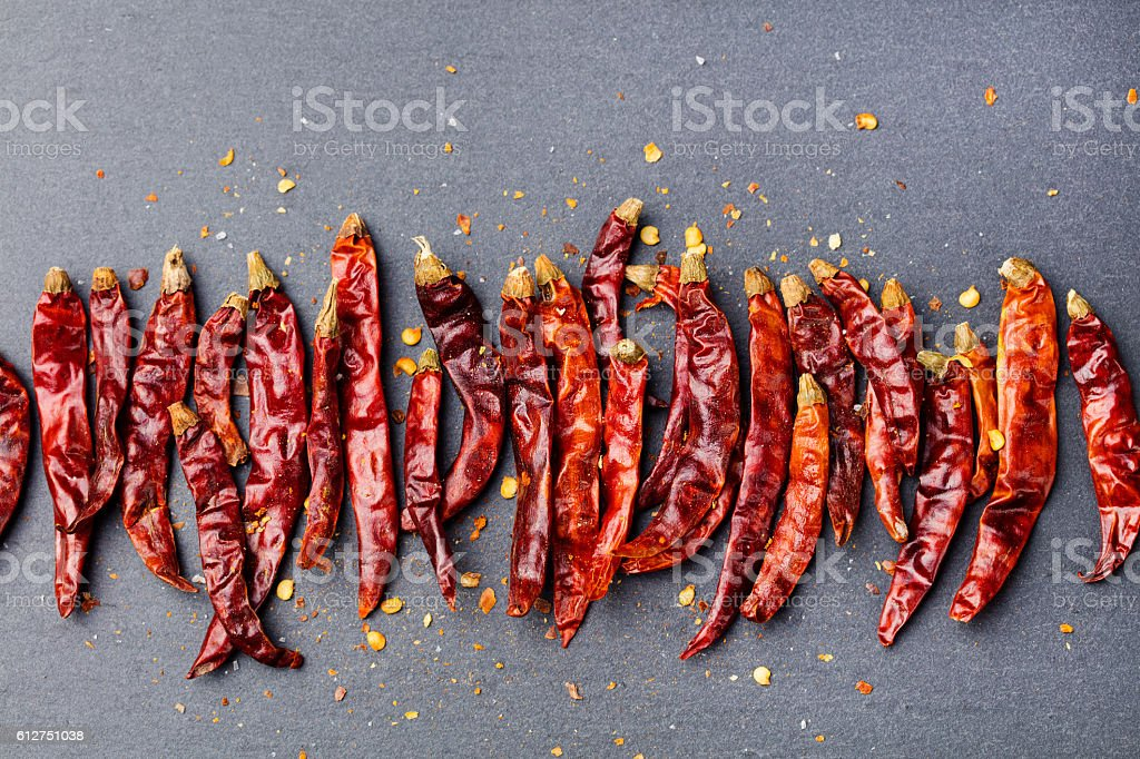 Dried red chili peppers on slate background. Copy space stock photo