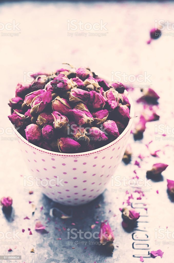 Dried rose buds in tea cup on light background stock photo