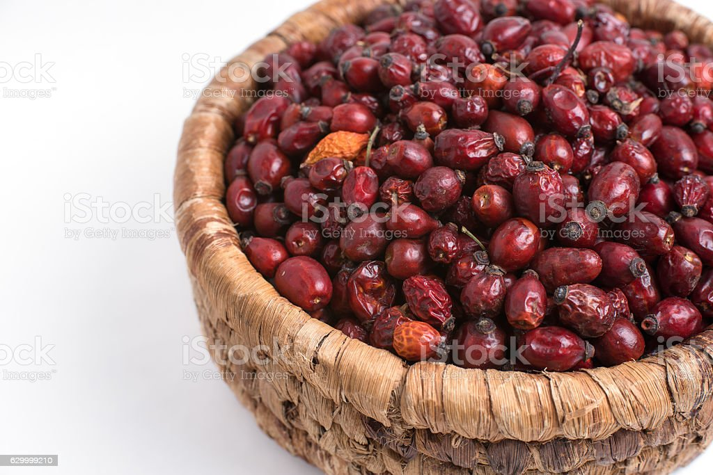 Dried rose hips in wicker basket isolated on white background stock photo