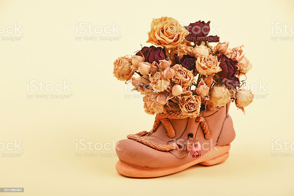 Dried roses bouquet in ceramic shoe royalty-free stock photo