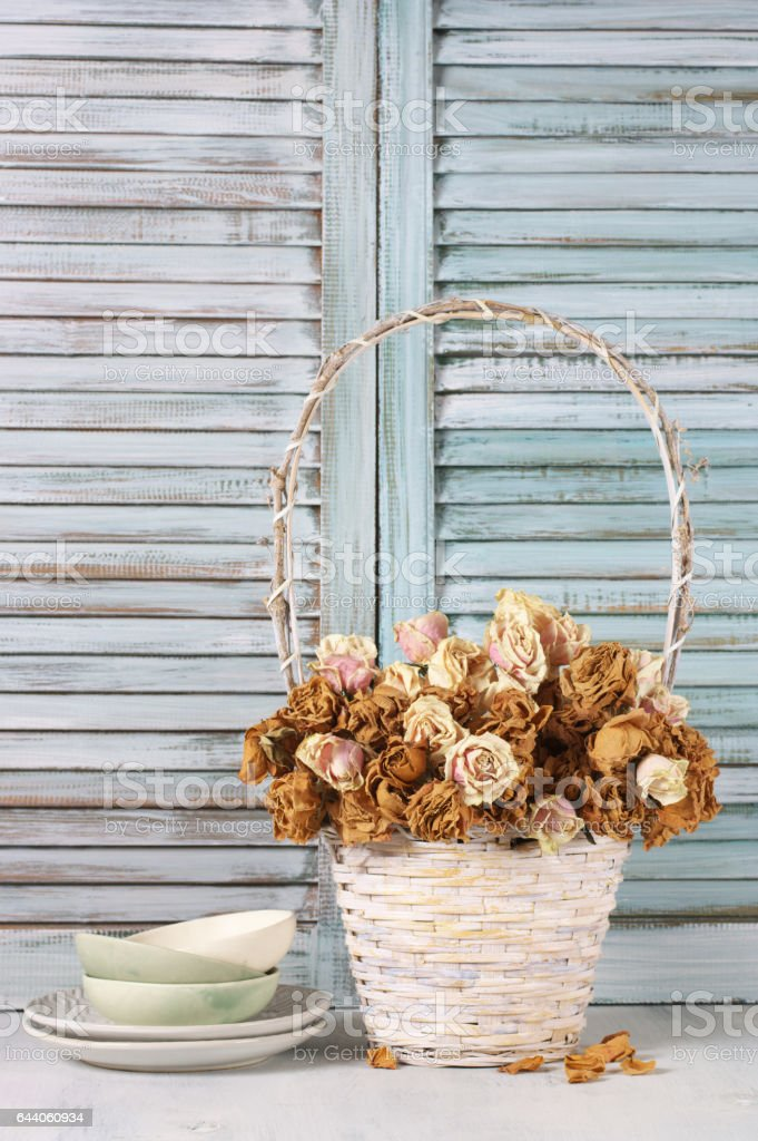 Dried roses in basket against blinds stock photo
