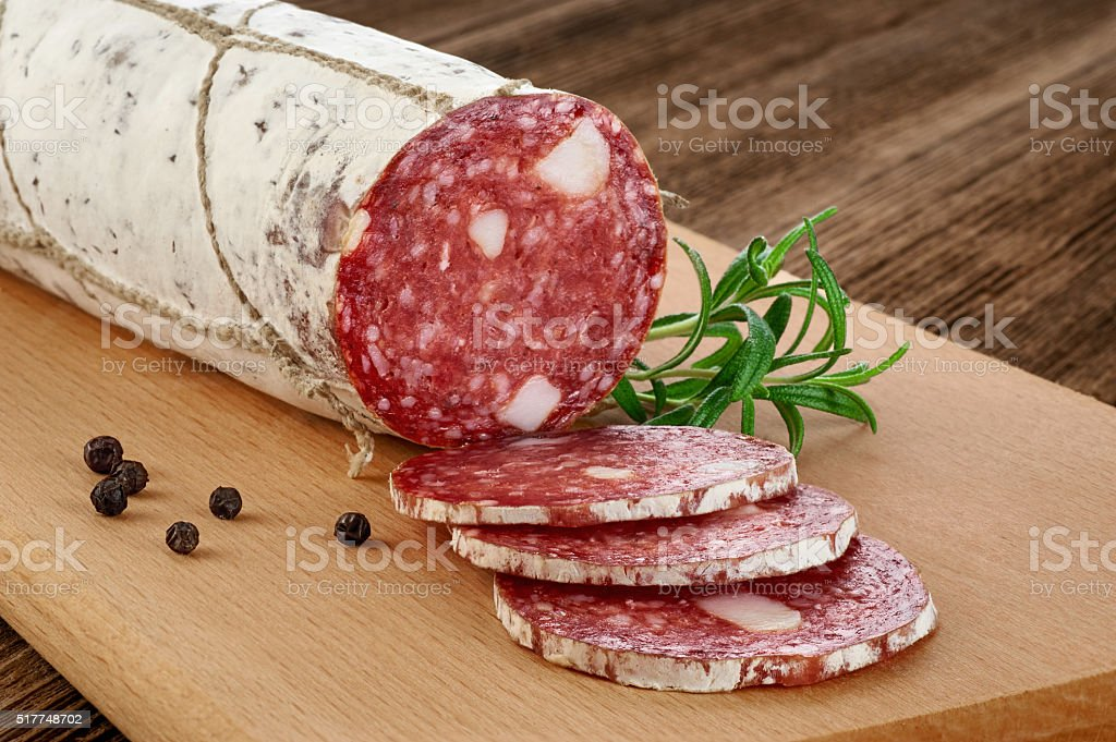 Dried salami with white mold on a wooden background. stock photo