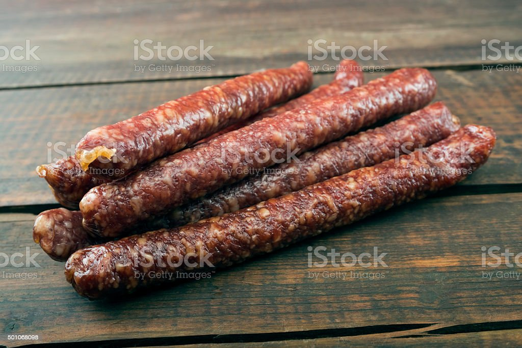 dried sausages on old wooden table stock photo