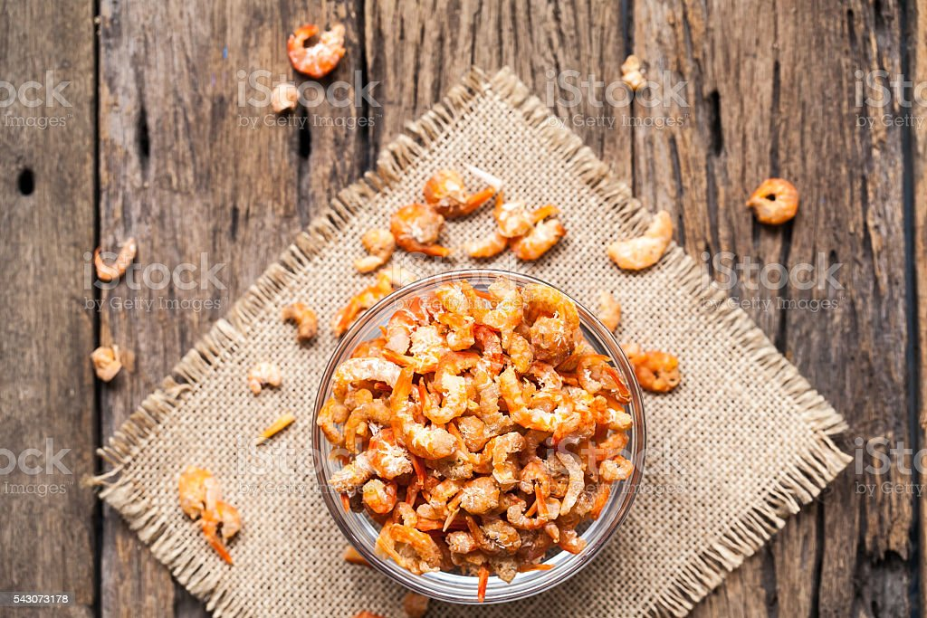 Dried shrimp in bowl on sackcloth stock photo