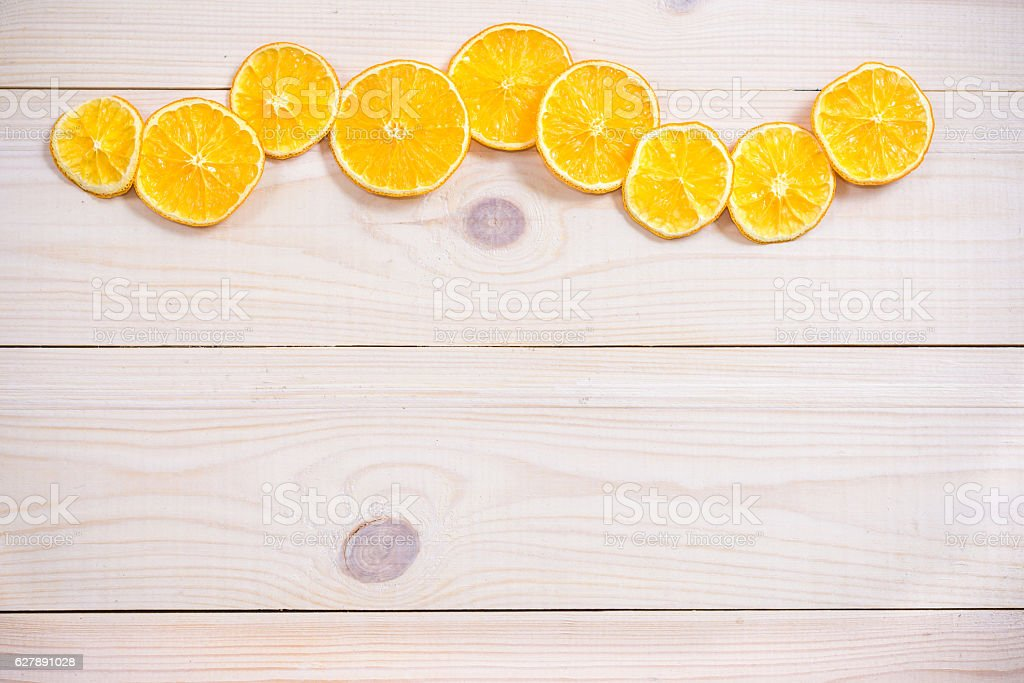 dried slices of orange over wooden background. texture. stock photo