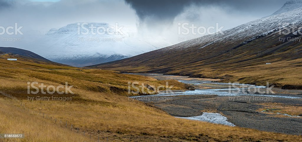 Dried stream between hill surround by yellow field stock photo