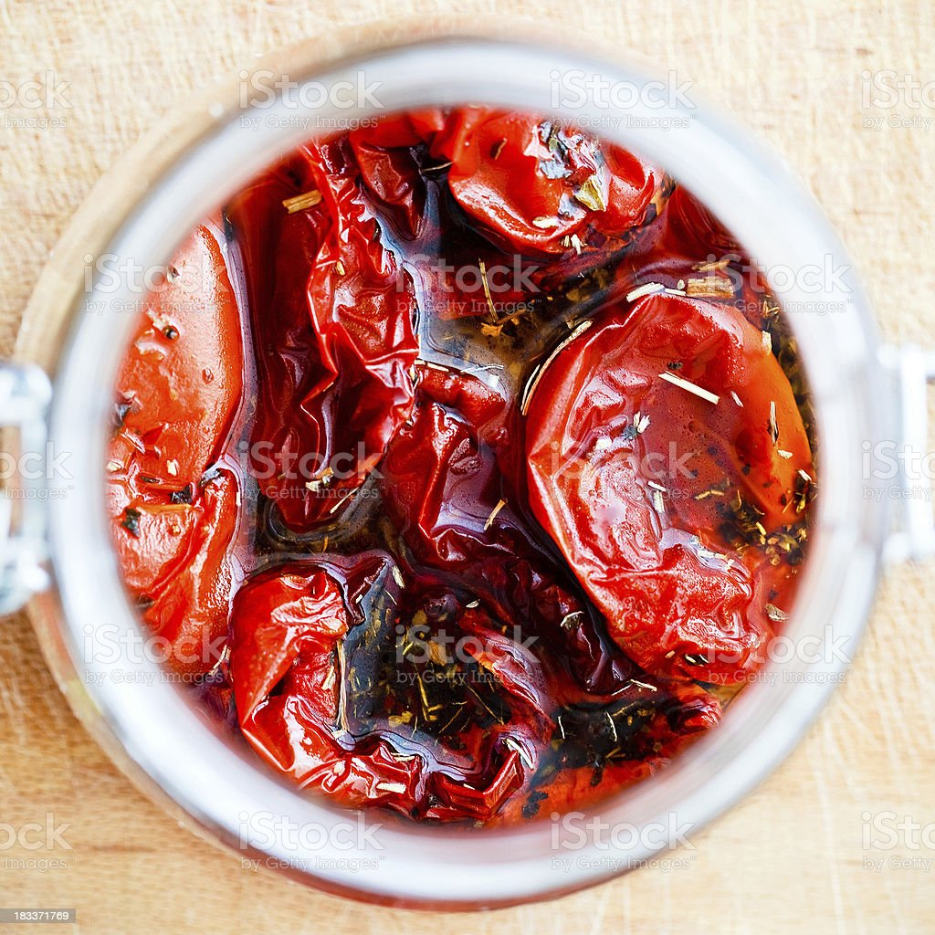 Dried tomatoes with olive oil and herbs stock photo