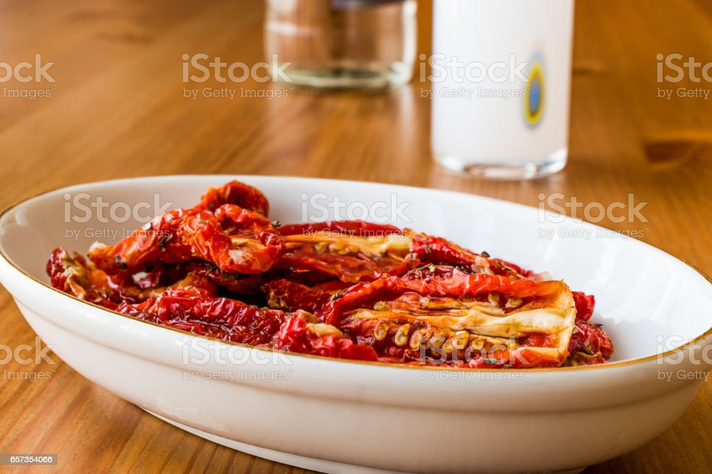 Dried tomatoes with Raki on wooden surface. stock photo