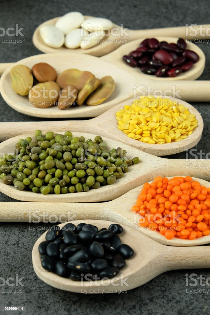Dried various beans and lentils in wooden spoons. stock photo
