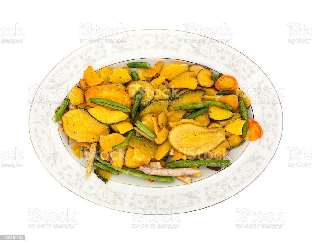 Dried vegetable chips on an old platter stock photo