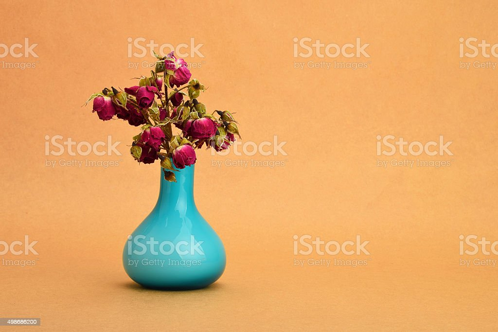 Dried-up red roses bouquet in blue vase on kraft paper royalty-free stock photo