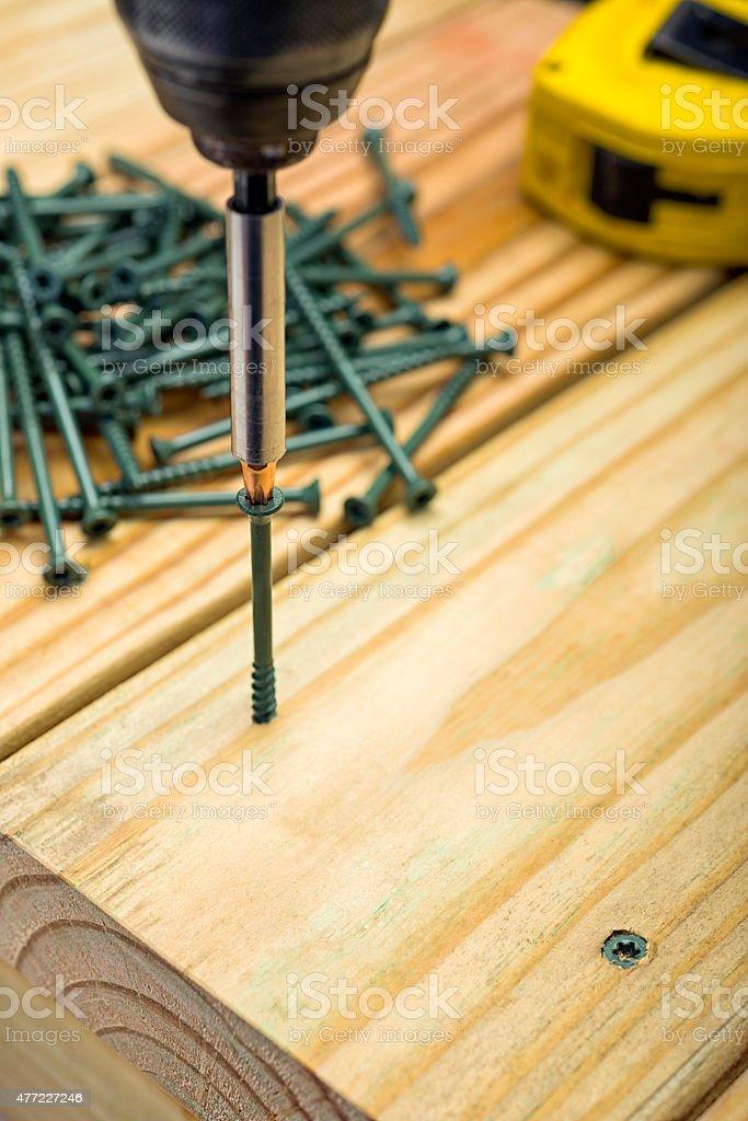 Drill driving Torx screws into a PT Deck Board stock photo