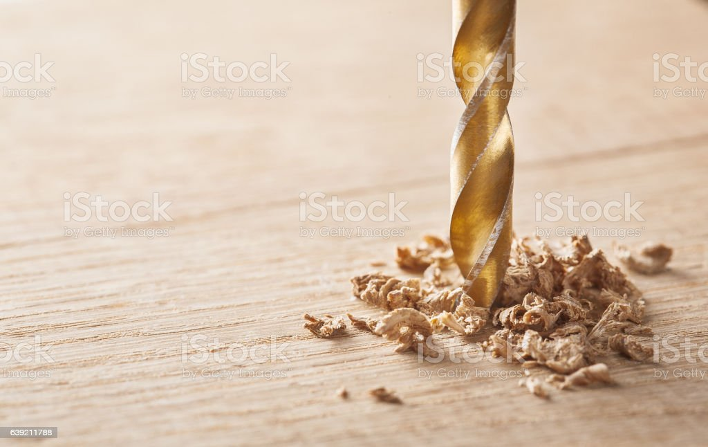 drill makes a hole in  wooden oak table stock photo