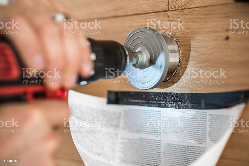 Drilling a hole in the wall stock photo