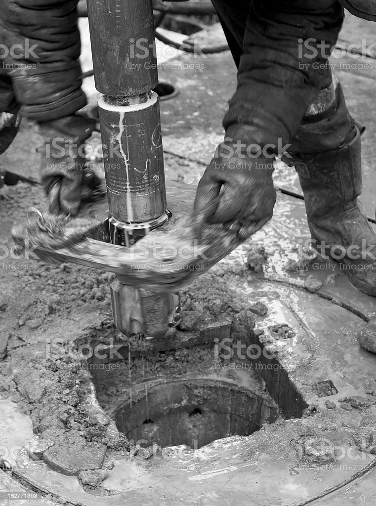 Drilling bit with motor at oil rig and roughneck hands royalty-free stock photo