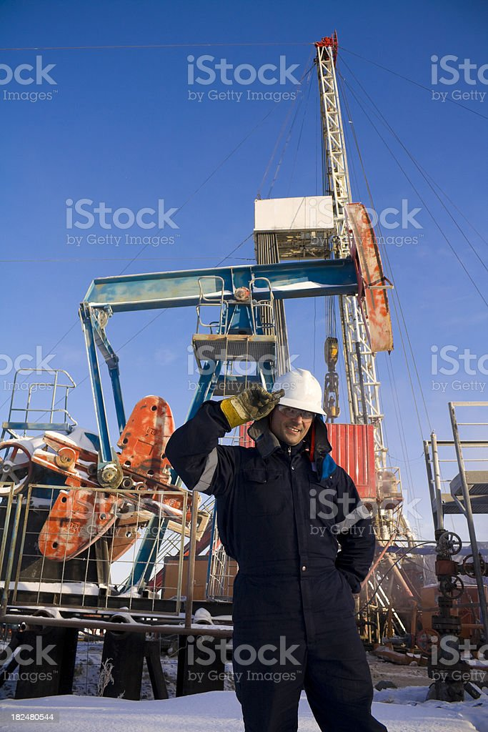 Drilling engineer at rig site with oil pump stock photo