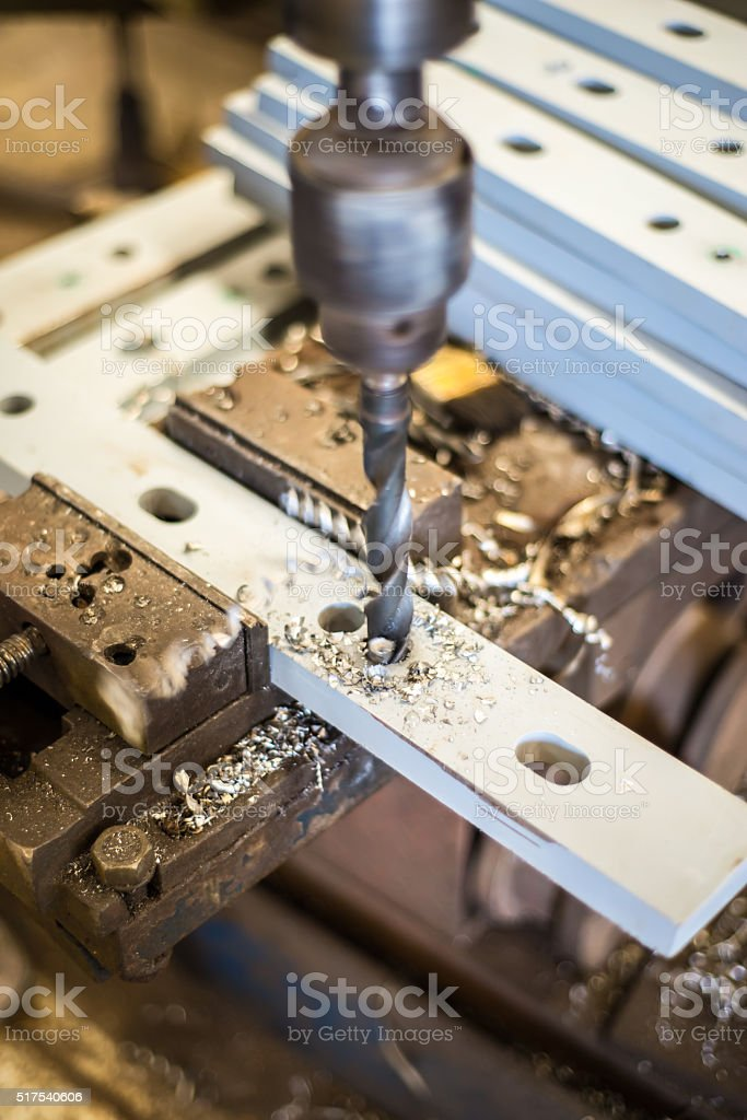 drilling in flat steel plate with bench drill. stock photo