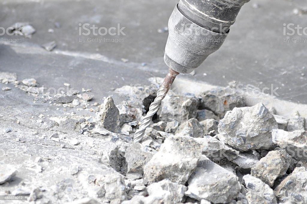 Drilling machine breaking concrete floor stock photo