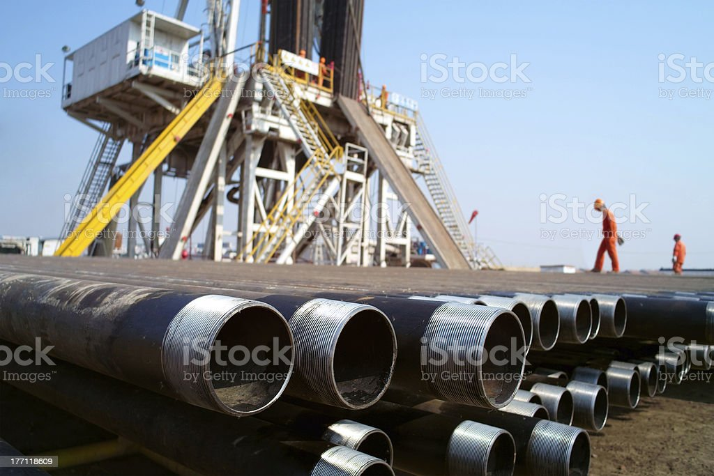 Drilling rig, pipes and workers stock photo