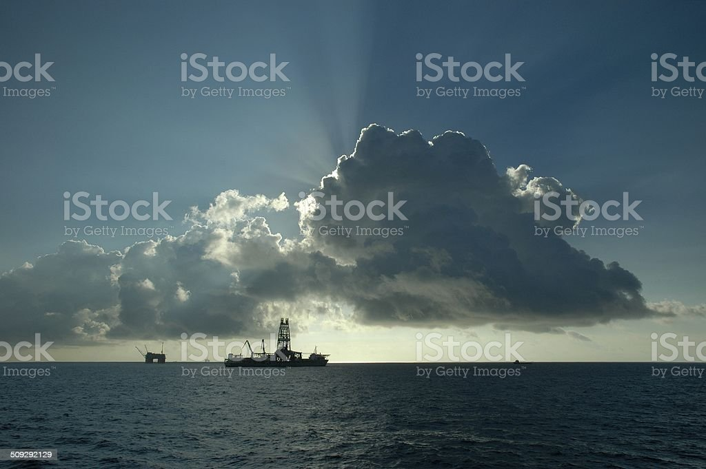 Drillship and production platform in distance stock photo