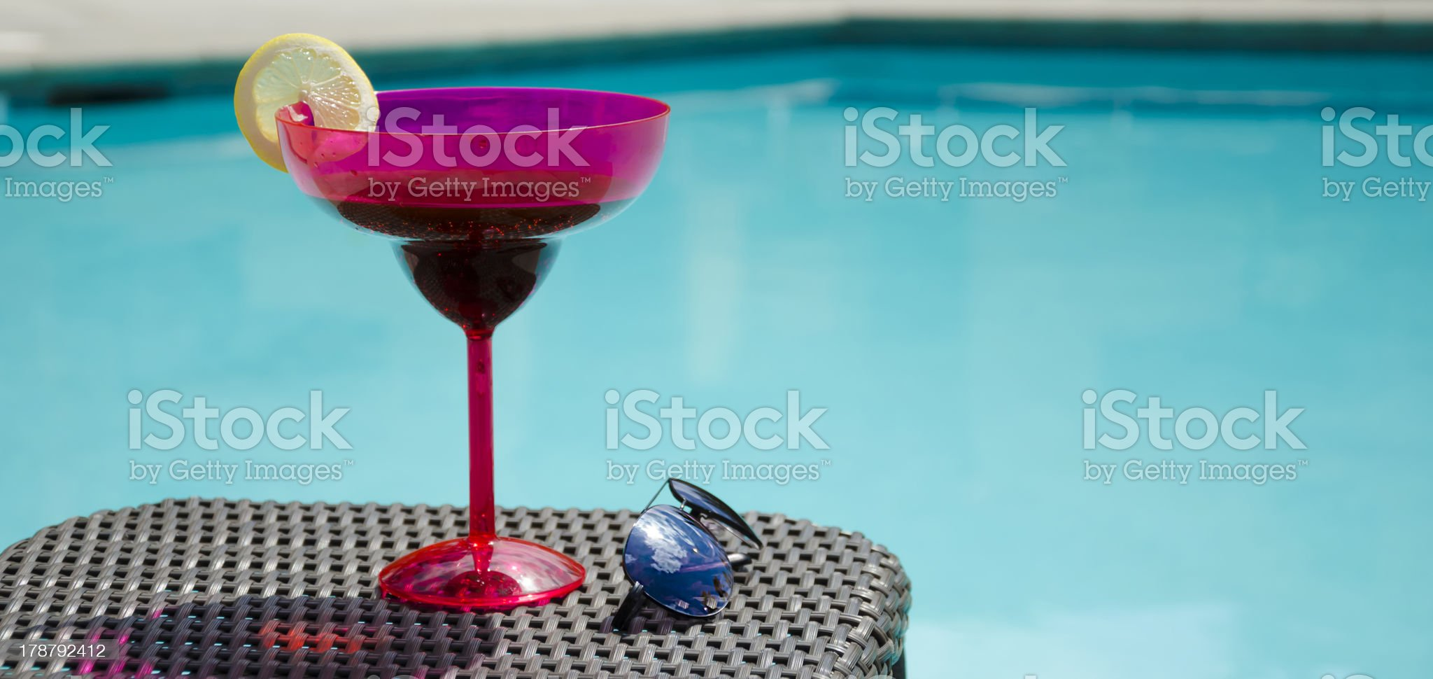 Drink and sunglasses by the pool royalty-free stock photo
