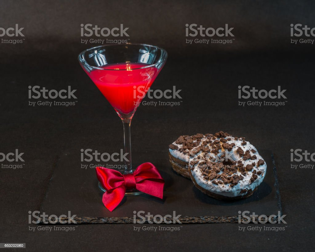 drink cosmopolitan a glass of martini decorated with a red bow with two doughnut on a black stone plate stock photo
