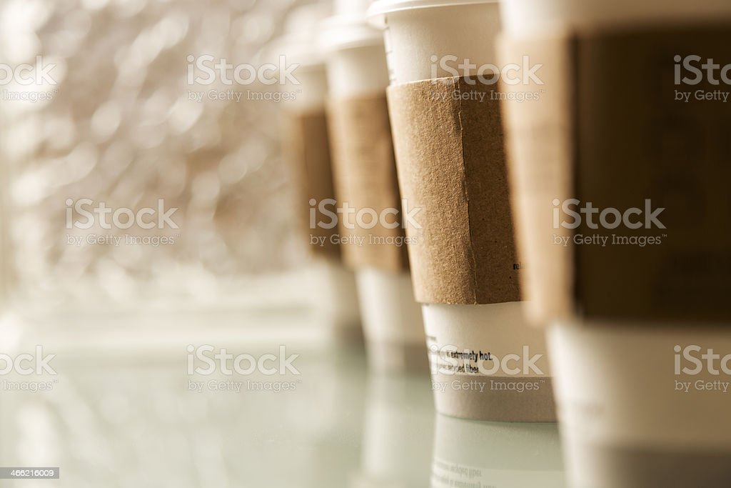Drink:  Cups of coffee in a row on glass table. stock photo