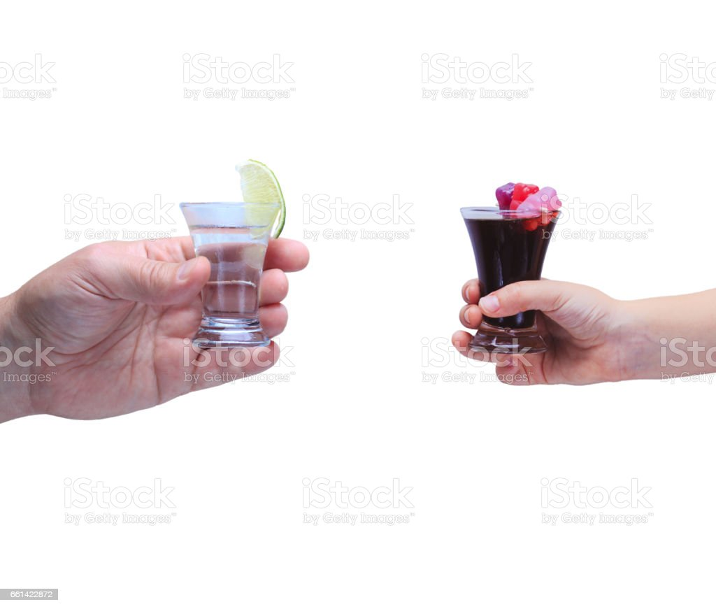 Drink responsibly!  Adult hand with shot of tequila and kid hand with cola and jelly bears stock photo