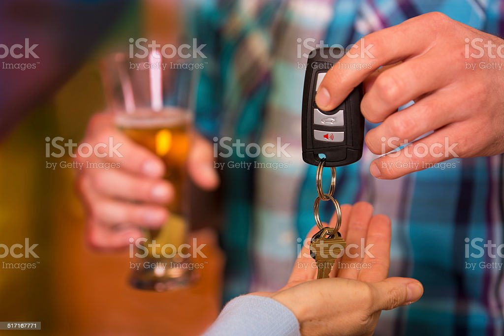 Drinking and Driving.  Man gives car keys to friend.  Beer. stock photo