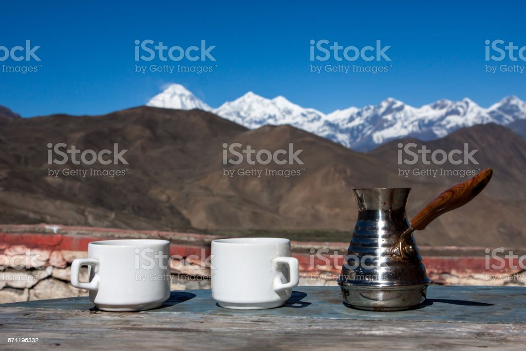 Drinking coffee with stunning mountain view. Beautiful Himalayas landscape with coffee cups and cezve. Drinking coffee outside on a background of snowy landscape. stock photo