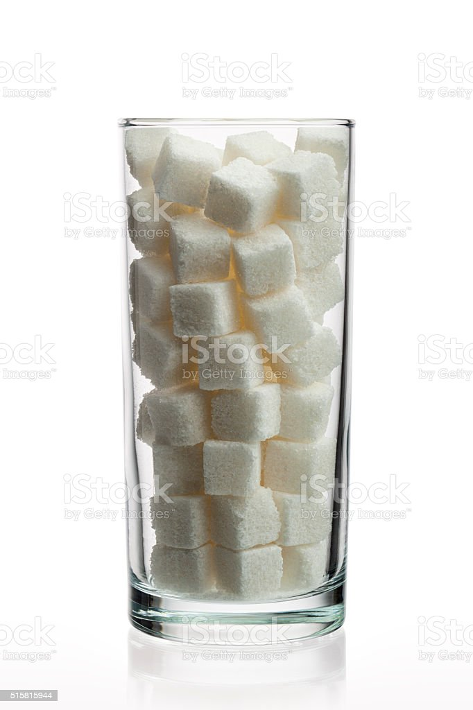 Drinking glass with sugar cubes stock photo