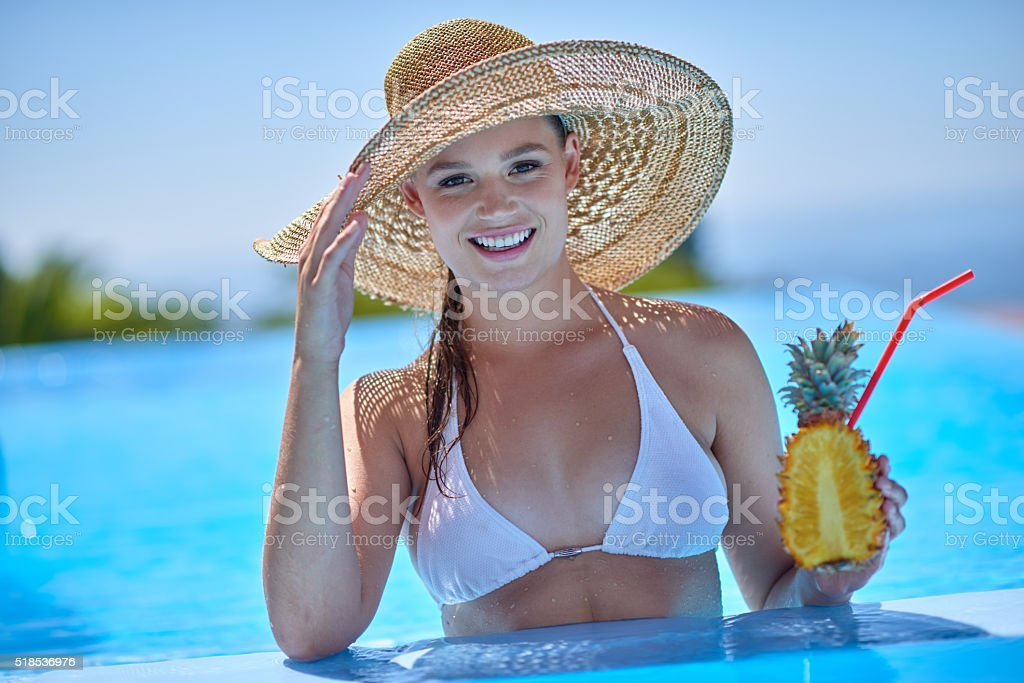 Drinking juice from pineaple while relaxing in swimming pool stock photo