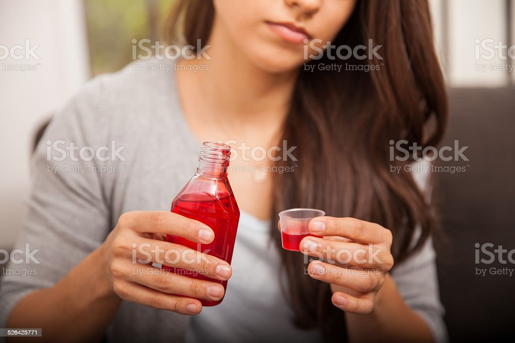 Drinking some cough syrup stock photo