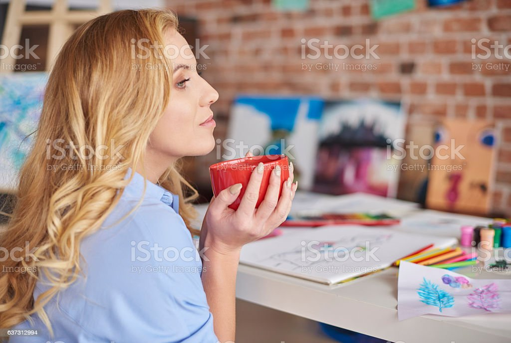 Drinking tea over her paintings stock photo