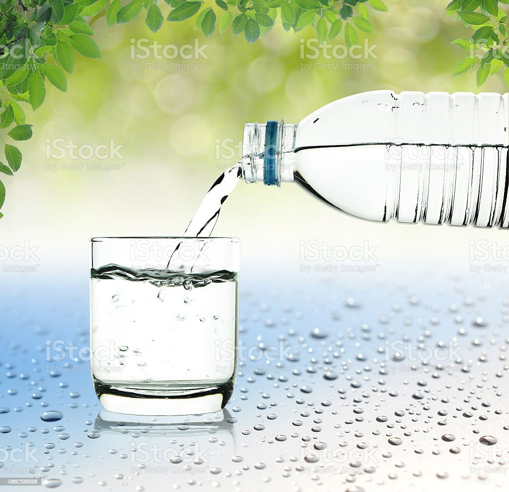 Drinking water is poured from a bottle into a glass stock photo