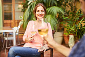 Drinking white wine with her husband in the garden.