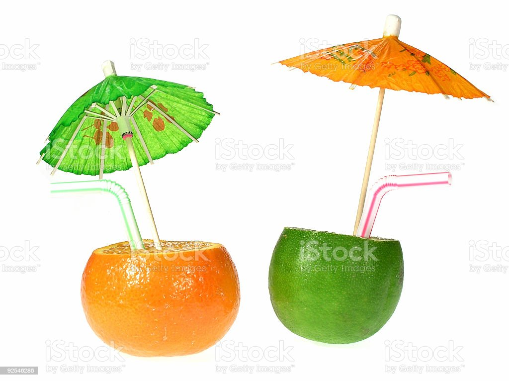 Drinks made out of a lime and an orange with mini umbrellas stock photo