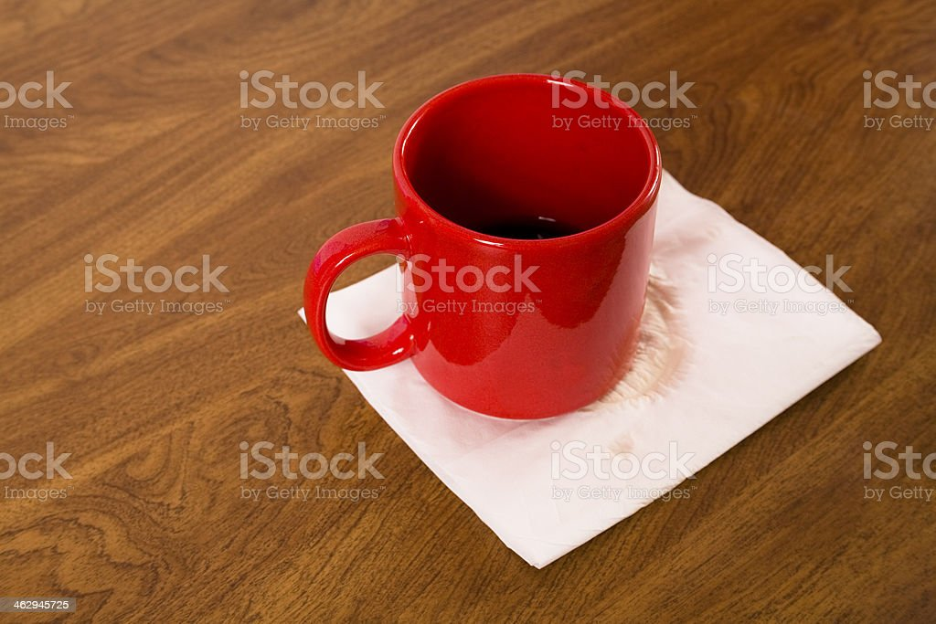 Drinks: Red coffee mug on wooden table. Napkin. royalty-free stock photo