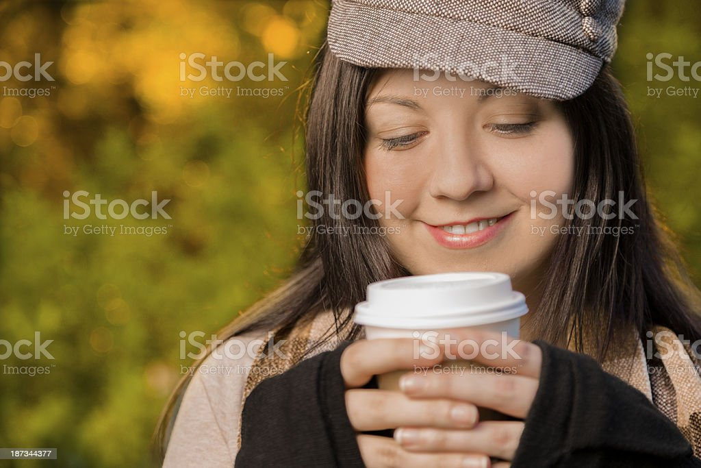 Drinks: Young woman holds hot coffee in autumn. royalty-free stock photo
