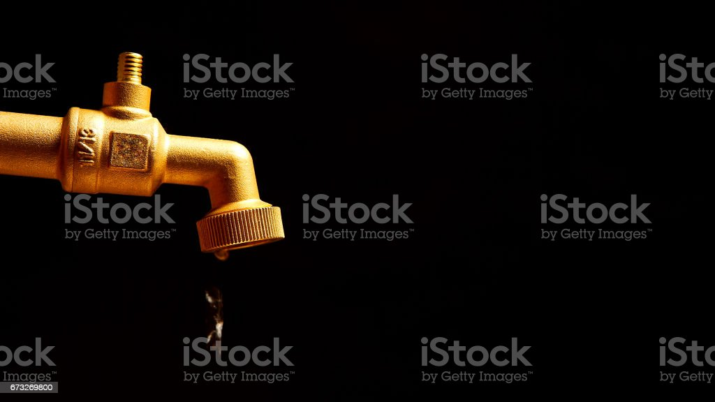 Dripping faucet on a black background stock photo