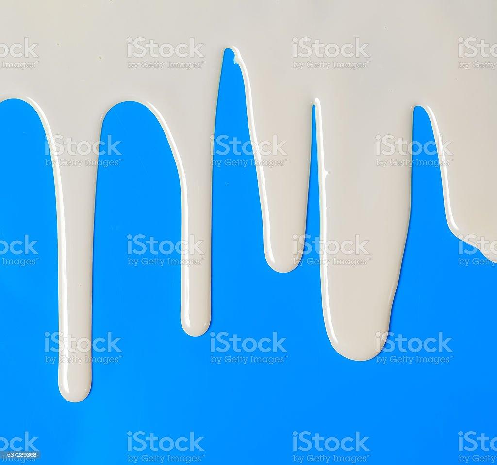 Dripping white milk, cream, paint yogurt on blue background stock photo