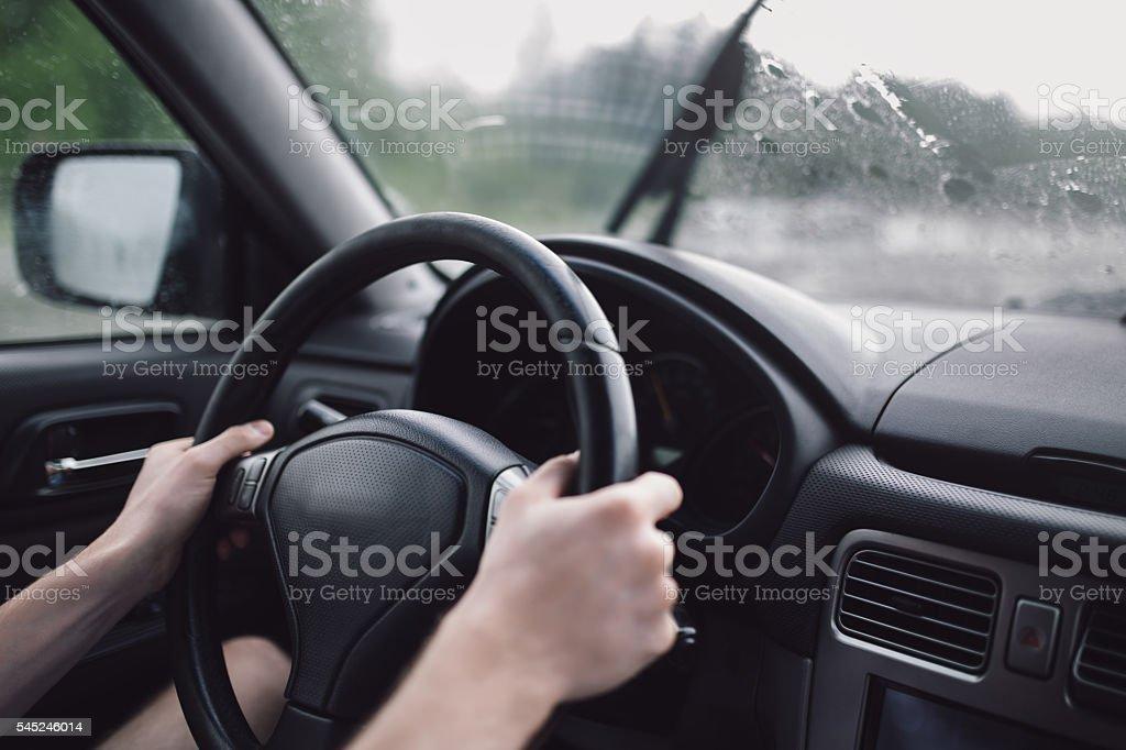 Drive car in rain. Hands on steering wheel stock photo