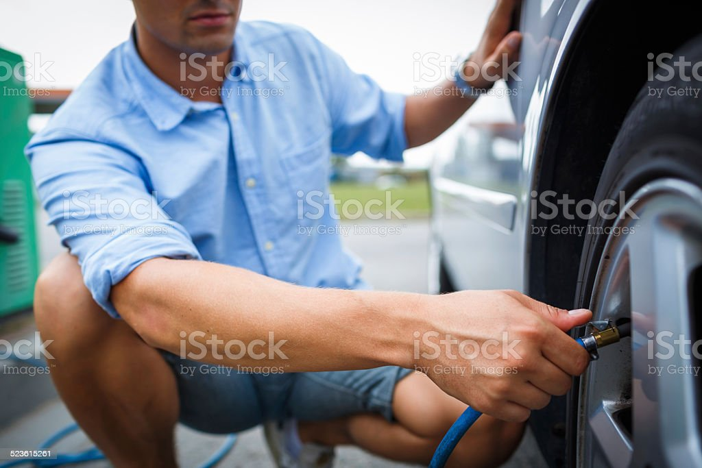 Driver checking air pressure in the wheel stock photo